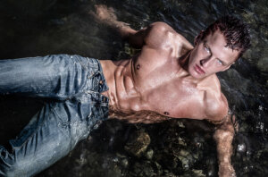 shirtless athletic man in water
